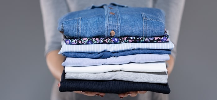 woman-holding-stack-of-folded-laundry